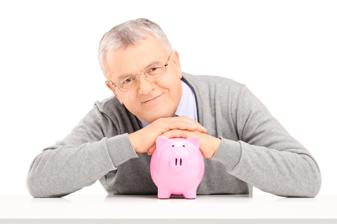 Satisfied mature gentleman posing over a piggy bank isolated on
